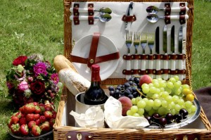 A family picnic basket containing grapes, strawberries, bread and wine