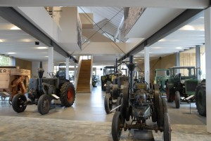 Glass exhibition hall with tractors – some vintage models – arranged in a 'herd'